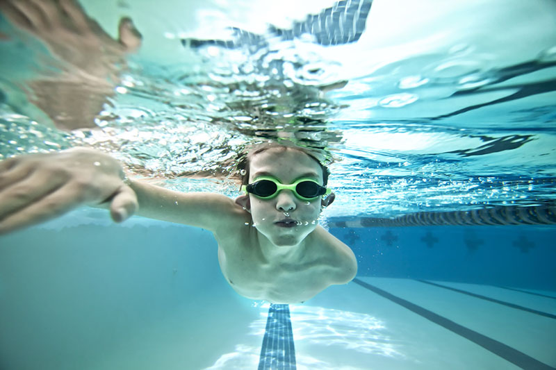boy swimming underwater after swim class